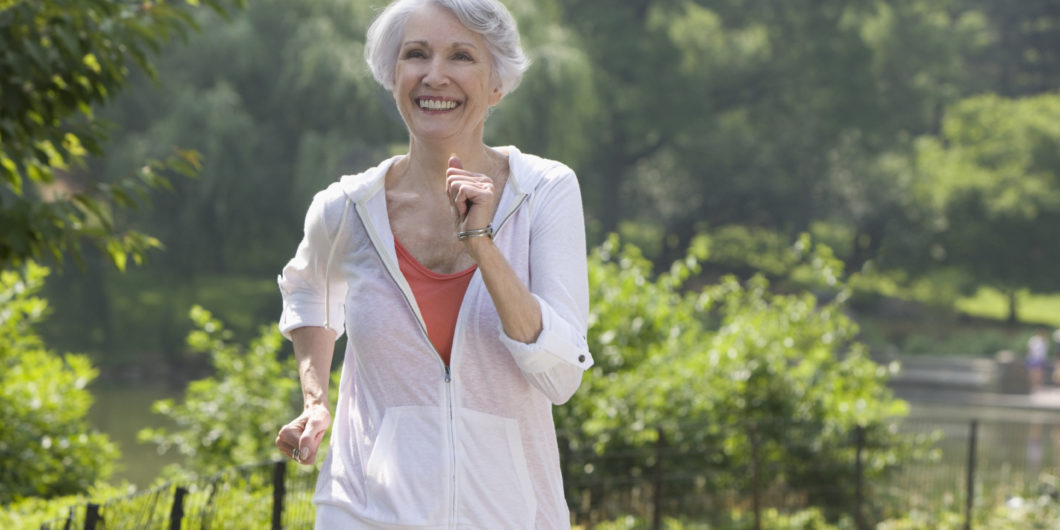 Active older woman walking confidently in the park