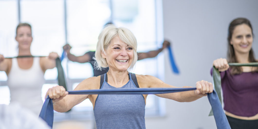 Image shows a senior lady working out with an exercise band in a fitness class